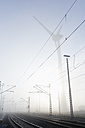 Germany, Hamburg, wind turbine next to railway track in early morning fog - MSF003981