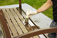 Man applying glaze on wooden bench, partial view - ONF000559