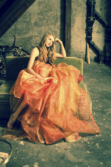 Portrait of young woman sitting at attic wearing orange skirt - FCF000225
