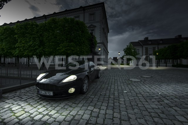Germany, North Rhine-Westphalia, Bensberg, Aston Martin Vanquish S with lighted headlights parking in front of Bensberg Castle - AM002277