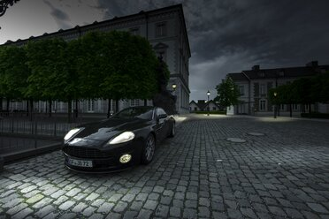 Germany, North Rhine-Westphalia, Bensberg, Aston Martin Vanquish S with lighted headlights parking in front of Bensberg Castle - AM002277
