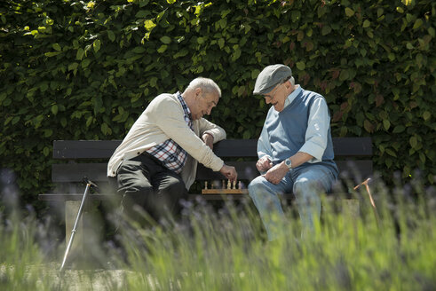 Two old friends sitting on park bench playing chess - UUF000736