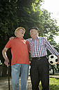 Two old friends walking in the park with football - UUF000712