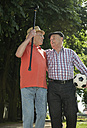 Two old friends walking in the park with football - UUF000715