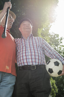 Two old friends walking in the park with football - UUF000716