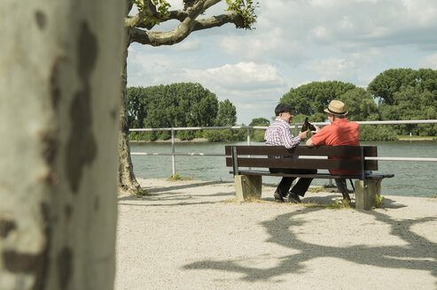 Germany, Rhineland-Palatinate, Worms, two old friends sitting on bench at promenade of Rhine River - UUF000723