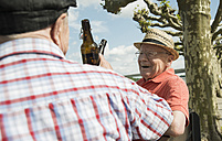 Two old friends toasting with beer bottles in the park - UUF000724