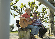 Germany, Rhineland-Palatinate, Worms, two old friends with guitar sitting on bench at promenade of Rhine River - UUF000727