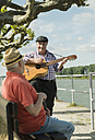 Germany, Rhineland-Palatinate, Worms, two old men with guitar at promenade of Rhine River - UUF000728