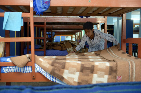Peru, Ayacucho, boy making the bed at dormitory of children's home - FLK000307