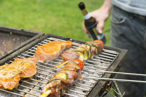 Man holding beer bottle at barbecue grill with meat - ON000594