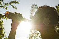 Man drinking beer from bottle in sunlight - ONF000596