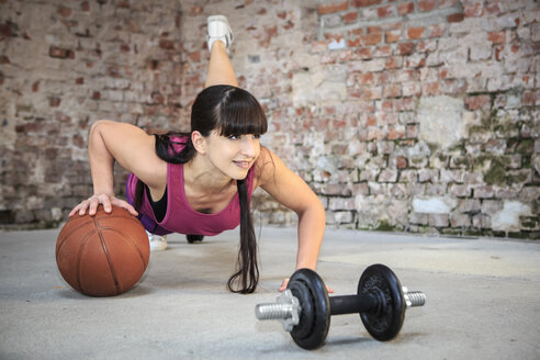 Woman with barbells doing fitness exercise in a gym - VTF000265