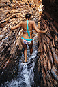 Australia, Western Australia, Karijini National Park, Hancock Gorge, woman in bikini walking through canyon, back view - MBEF001019