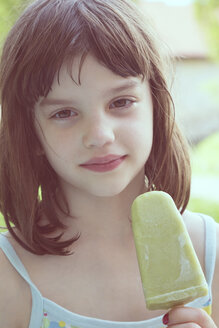 Portrait of daydreaming girl with green ice lolly - LVF001357
