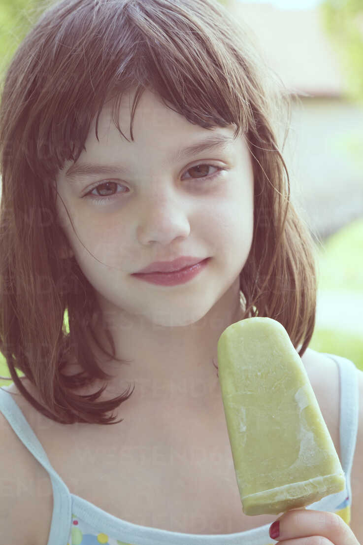 Portrait of daydreaming girl with green ice lolly - LVF001357 - Larissa Veronesi/Westend61