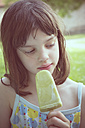 Portrait of daydreaming girl with green ice lolly - LVF001358