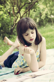 Portrait of little girl lying on blanket in the garden writing diary - LVF001362