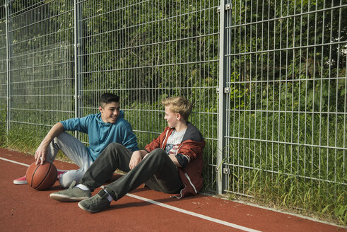 Two boys with basketball leanaing against fence - UUF000771