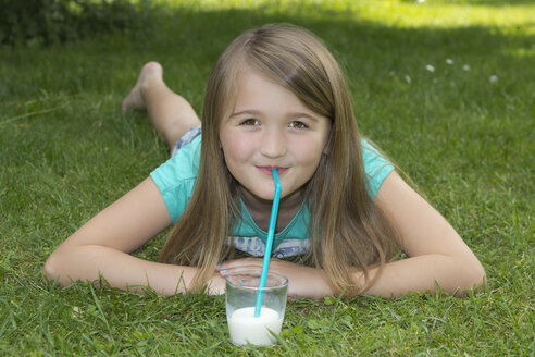 Girl lying on meadow drinking milk with drinking straw - YFF000157