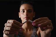 Young woman breaking a cigarette in front of black background - BFRF000452