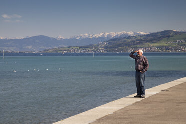 Switzerland, Thurgau, Arbon, One senior man standing at lakeside promenade - WIF000735