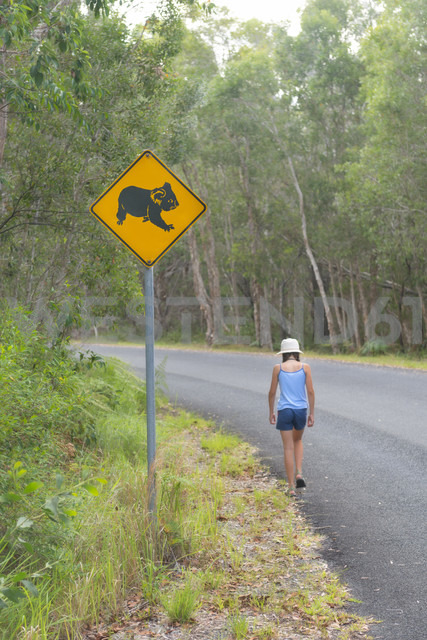 Australia, New South Wales, Pottsville, roadsign with a koala bear and girl walking along road in Pottsville Environmental Park - SHF001338