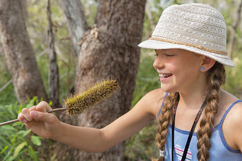 Australia, New South Wales, Pottsville, girl with hat with an Australian Banksia plant flower - SHF001400