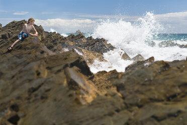 Australia, New South Wales, Byron Bay, Broken Head nature reserve, boy on rocks with breaking waves in front - SHF001344