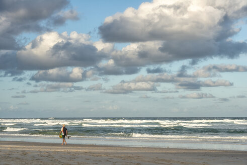 Australia, New South Wales, Pottsville, angler walking along beach with surf and dark clouds - SH001367