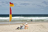 Australia, New South Wales, Pottsville, beach with saftey flag and tourists reading - SH001380
