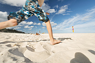 Australia, New South Wales, Pottsville, boy running in sand on beach - SHF001390