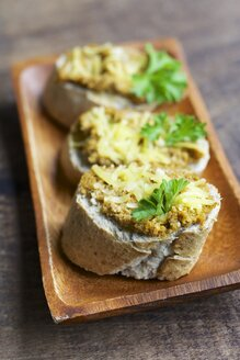 Slices of baguette with a carrot walnut spread and vegan cheese on a chopping board - HAWF000240