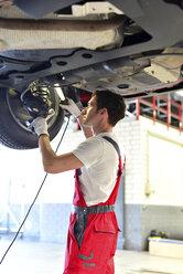 Car mechanic in a workshop working at car - LYF000050