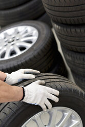 Close-up of car mechanic with tires - LYF000053