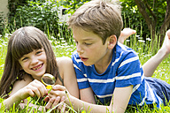 Portrait of brother and sister lying on meadow in the garden having fun with magnifying glass - LVF001374