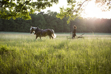 Germany, Brandenburg, Bienenwerder,  female farmer on the way to a field with her horse - FX000003