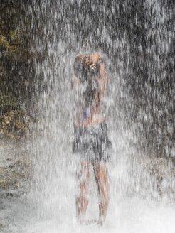 Antilles, Lesser Antilles, Saint Lucia, Soufriere, young woman refreshing under waterfall - AM002315