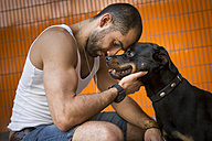 Portrait of young man head to head with his Rottweiler - FX000017