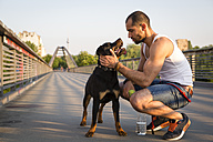 Germany, Berlin, portrait of young man playing with his Rottweiler on pedestrian bridge - FX000013