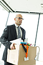 Businessman carrying cardboard box in office - WESTF019267