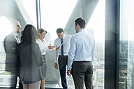 Businesspeople in office with woman using digital tablet - WEST019277