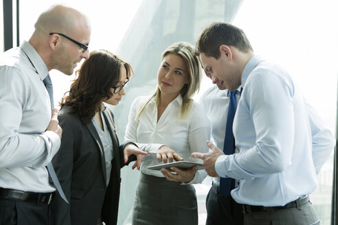 Businesspeople in office with woman using digital tablet - WESTF019280