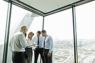 Businesspeople in office with woman using digital tablet - WESTF019310