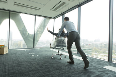 Businessman pushing businesswoman in office chair - WESTF019326