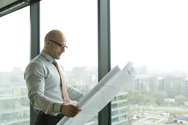 Businessman in office looking at blueprint - WESTF019330