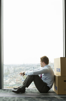 Businessman leaning against cardboard boxes looking out of window - WESTF019502