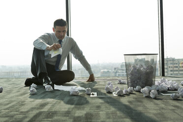 Businessman sitting on office floor surrounded by crumpled paper - WESTF019298