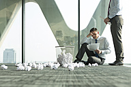 Two businessmen on office floor surrounded by crumpled paper - WESTF019301