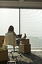 Businesswoman using laptop with feet on cardboard boxes - WESTF019517